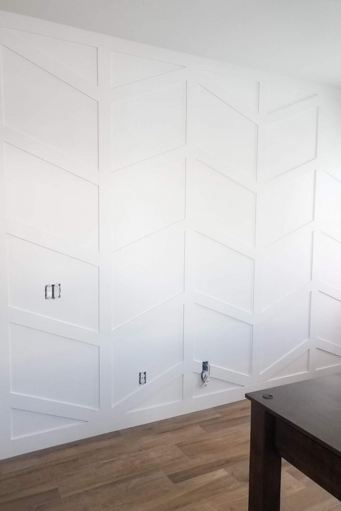 Herringbone accent wall with moldings and trim